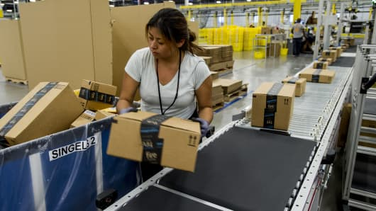 An Amazon.com Inc. employee lifts a box from a conveyor at the company's fulfillment center in Tracy, California.