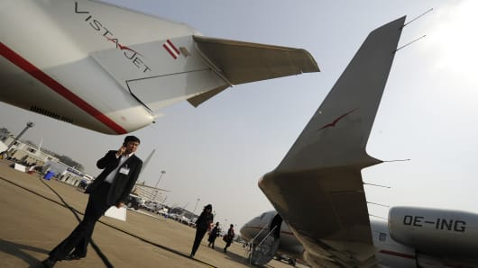 Visitors look at an aircraft from air charter company Vistajet and a Vistajet Boeing aircraft.