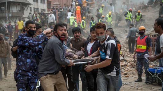Emergency rescue workers carry a victim on a stretcher on April 25, 2015 in Kathmandu, Nepal.
