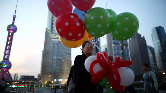 A woman holding balloons walks near Oriental Pearl Radio & TV Tower in Shanghai