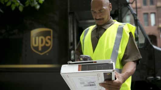 United Parcel Service (UPS) employee Eric Brooks scans a package while making a delivery in Washington, D.C.
