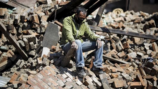 A man sits on the rubble of his damaged house following Saturday's earthquake in Bhaktapur, Nepal April 27, 2015.