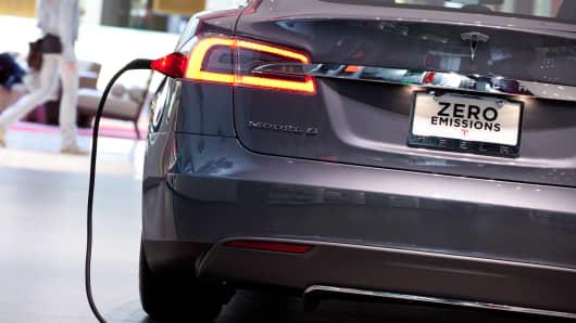 A Tesla Model S charging in a showroom.