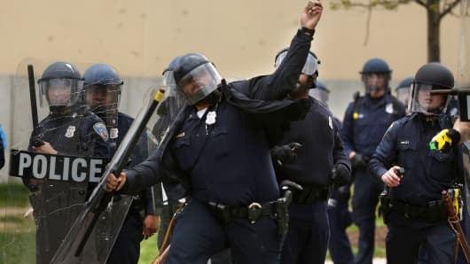 A Baltimore Police officer throws a rock back at violent protesters outside the Mondawmin Mall following the funeral of Freddie Gray April 27, 2015 in Baltimore, Maryland.