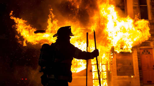 A Baltimore firefighter attacks a fire at a convenience store and residence during clashes after the funeral of Freddie Gray in Baltimore, Maryland in the early morning hours of April 28, 2015.