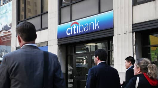Pedestrians walk in front of a Citibank branch in New York.