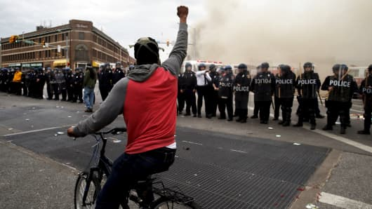 A protester on a bicycle thrusts his fist in the air next to a line of police in front of a burning CVS drug store during clashes in Baltimore on April 27, 2015.