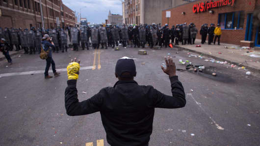 A man with his hands up as officers move forward during a protest for Freddie Gray in Baltimore, April 27, 2015.