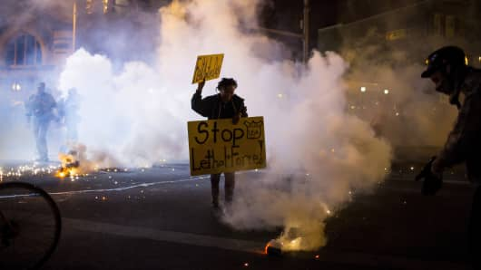 A protester holds a sign as clouds of smoke and crowd control agents rise, shortly after the deadline for a city-wide curfew passed in Baltimore, Maryland April 28, 2015, as crowds protest the death of Freddie Gray, a 25-year-old black man who died in police custody.