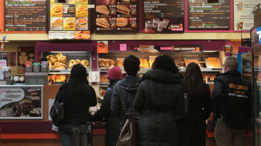 People wait in line in the morning at a Dunkin' Donuts chain restaurant in New York City.