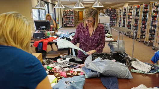 Workers in the Moxie Jean office sorting clothes before they are listed and sold.