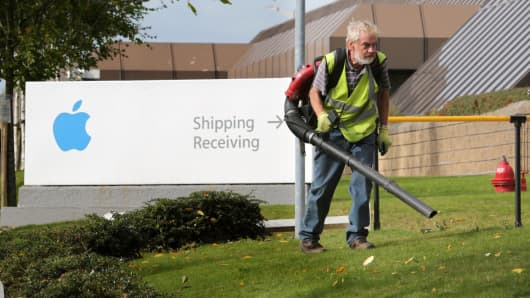 A man clears away leaves outside buildings on The Apple campus in Cork, southern Ireland.