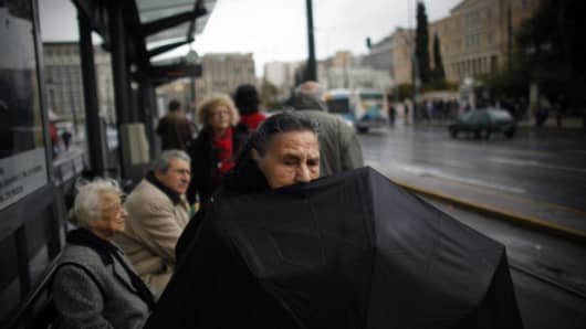 Pedestrians shelter from the rain as they wait for a tram in central Athens, Greece.