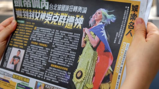 In this photo illustration taken on April 30, 2015, a local resident reads a newspaper showing US singer Katy Perry wearing Taiwan's national flag in Taipei. The intricacies of the 'one China' policy may not have been uppermost on her mind, but US pop star Katy Perry caused a stir in Asia this week with her politically-charged choice of dress at a Taipei concert.