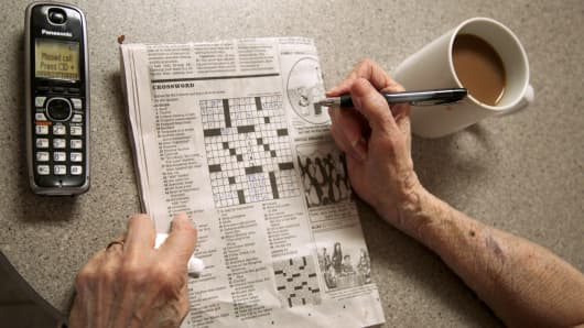 Elderly woman does crosswords as she ignores a call on her phone.