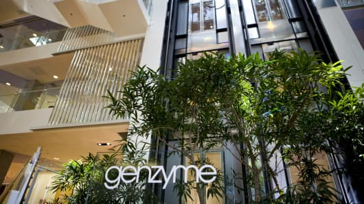 Signage sits on display in an atrium at Genzyme Corp.'s headquarters in Cambridge, Massachusetts.