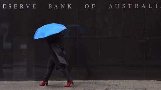 A woman walks past the Reserve Bank of Australia sign in Sydney, Australia.