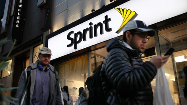 Pedestrians walk past a Sprint retail location in New York.