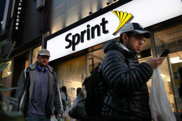 Pedestrians pass in front of a Sprint store in New York