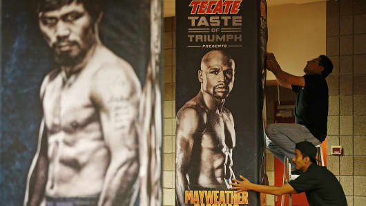 Workers install signs for an upcoming bout at the MGM Grand Garden Arena, April 27, 2015, in Las Vegas. Floyd Mayweather Jr. and Manny Pacquiao are scheduled to fight May 2.