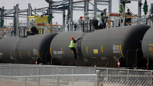 Employees fill a tank cars with oil at the Musket Windsor Crude Terminal in Windsor, Colorado, in April.