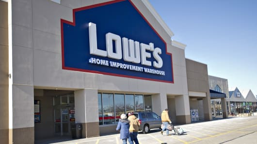 People walk outside a Lowe's store in East Peoria, Ill.