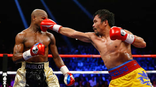 Manny Pacquiao throws a right at Floyd Mayweather Jr. during their welterweight unification championship bout on May 2, 2015 at MGM Grand Garden Arena in Las Vegas, Nevada.