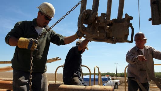 Workers install a new drill pipe in search of water at a farm near Mendota, Calif.