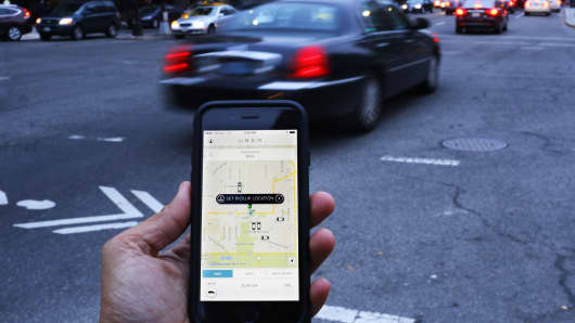 An UBER application is shown as cars drive by in Washington, DC.