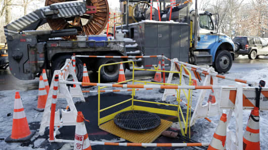 A Con Edison repair crew has set up a work site surrounding a manhole cover, Tuesday, Feb. 3, 2015 in the Brooklyn borough of New York. An electrical fire beneath the manhole cover caused an explosion on Monday that blew the cover into the air, striking a man in the head, causing serious injury.