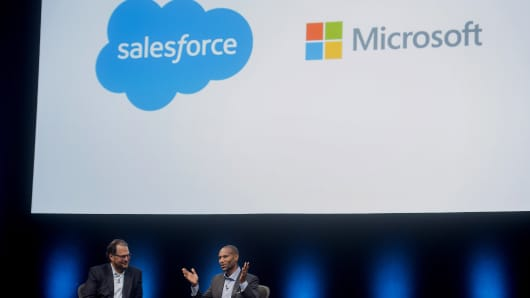 Marc Benioff, chairman and chief executive officer of Salesforce.com Inc. (left), speaks with Tony Prophet, vice president of Windows marketing at Microsoft Corp.