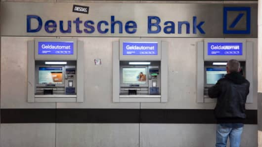 A customer uses an automated teller machine (ATM) outside a Deutsche Bank AG branch in Munich