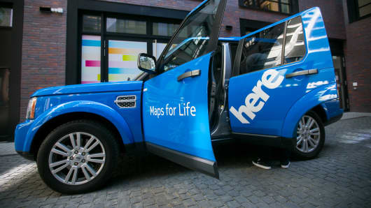 The logo of Nokia Oyj's connected driving maps unit HERE sits on the rear passenger door of a Land Rover SUV automobile, produced by Tata Motors Ltd.'s Jaguar Land Rover unit, outside the HERE offices in Berlin.