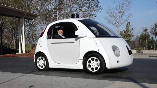 Google Chairman Eric Schmidt sits in a Google self-driving car at the Google headquarters in Mountain View, California.