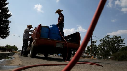 Residents fills buckets with non-potable water from a tank set up in front of the Doyle Colony Fire Station on April 23, 2015, in Porterville, California. Private wells here have gone dry.