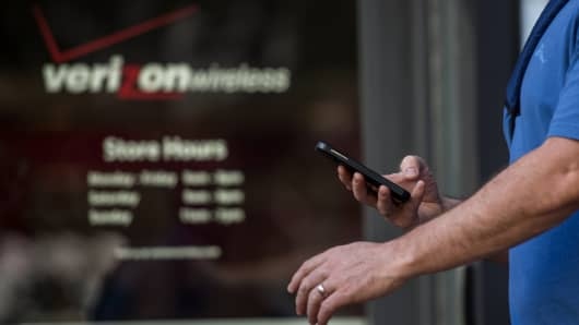 A pedestrian checks his mobile phone while walking past a Verizon Wireless store in San Francisco, California.