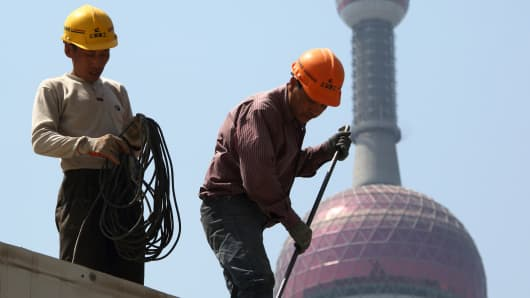 Workers labor in front of the Oriental Pearl Radio & TV Tower at a construction site in the Lujiazui district of Shanghai.