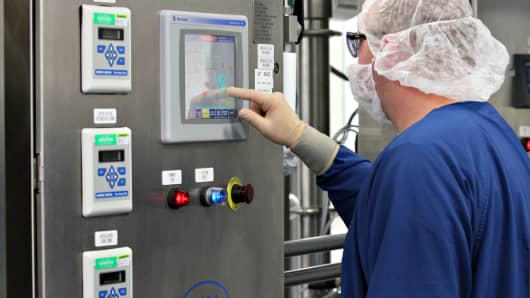 A worker uses a machine made by Pall Corp. during a demonstration of the clarification stage of the production of influenza vaccine during a tour at a Sanofi Pasteur vaccine production facility in Swiftwater, Pennsylvania.