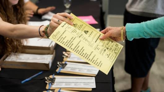 A representative, left, hands a list of employment descriptions to a job seeker during the Choice Career Fair in San Antonio, Texas.