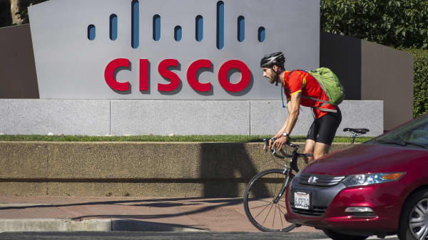 A bicyclist rides past Cisco Systems signage at the company's headquarters in San Jose, California.