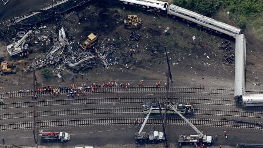 Investigators and first responders work near the wreckage of Amtrak Northeast Regional Train 188, from Washington to New York, that derailed yesterday May 13, 2015 in north Philadelphia, Pennsylvania.