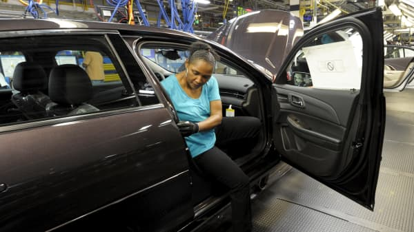 An auto worker installs a door gasket onto a 2015 Chevrolet Malibu being manufactured at GM's Fairfax assembly plant in Kansas City, Kansas May 4, 2015.