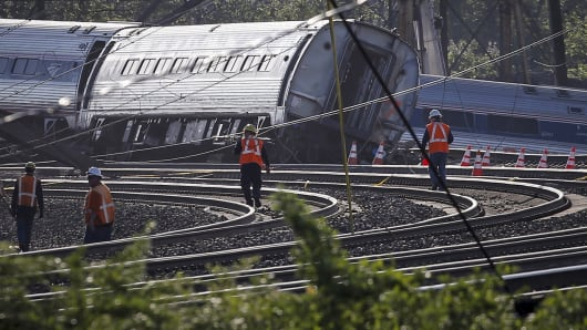Men walk towards the site of a derailed Amtrak train in Philadelphia, May 13, 2015.
