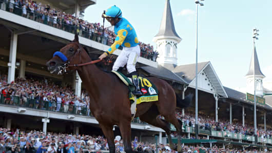 Jockey Victor Espinoza celebrates as he guides American Pharoah to win the 141st running of the Kentucky Derby at Churchill Downs on May 2, 2015, in Louisville, Kentucky.