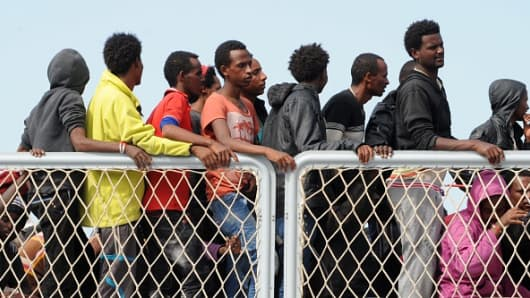 Migrants wait to disembark from military ship 'Bettica' after a rescue operation at sea on May 5, 2015 in the port of Salerno, southern Italy.