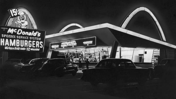 circa 1955: Exterior view of the first McDonald's fast food restaurant with its neon arches illuminated at night, Des Plaines, Illinois.