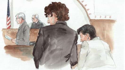 In this courtroom sketch, Dzhokhar Tsarnaev, center, is depicted with defense attorney Miriam Conrad, right, as the verdict is read by the clerk during his federal death penalty trial, May 15, 2015.