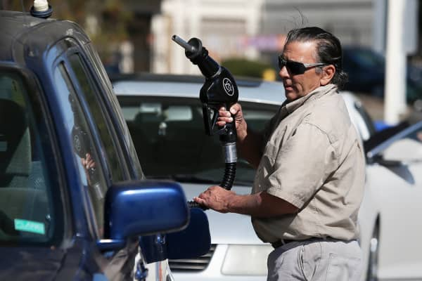 A customer prepares to pump gasoline at an Arco gas station in Mill Valley, Calif.