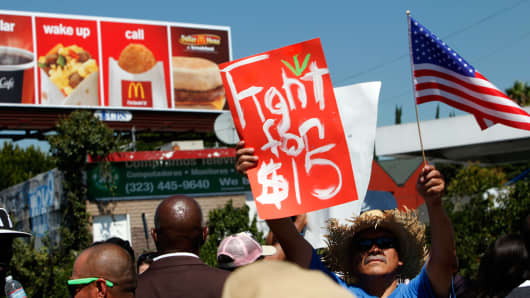 Fast-food workers and supporters organized by the Service Employees International Union (SEIU) protest in front of a McDonald's billboard in Los Angeles, in 2013.