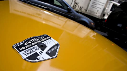 A New York City Taxi and Limousine Commission medallion sits on the hood of a taxi in New York.
